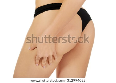 Sexy woman touthing her butt in panties, isolated on white. - stock photo