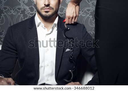 Sexy woman trying seduce rich businessman on sofa at night, bdsm - stock photo