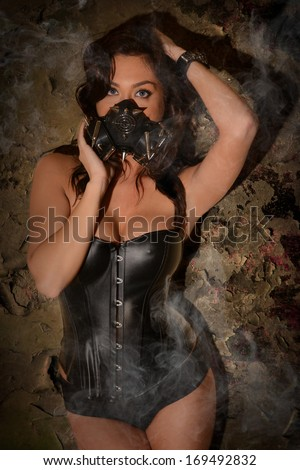 Sexy Woman wearing a Spiked Ammo Gas Mask and black Corset - stock photo