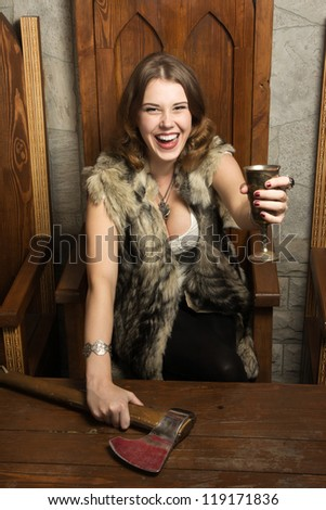 Sexy woman with a cup of wine in a medieval castle interior - stock photo