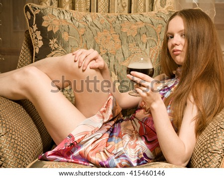 Sexy woman with glass of wine sitting on  armchair at home - stock photo