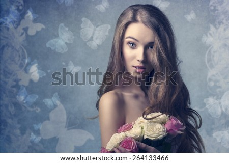 sexy woman with long natural hair posing with surprised expression, looking in camera and taking bouquet of roses in the hands  - stock photo