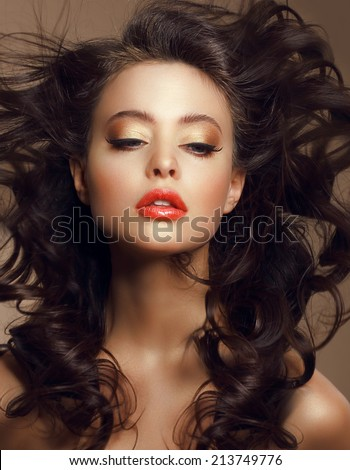 Sexy Woman with Long Windy Brown Hair and Saturated Makeup - stock photo