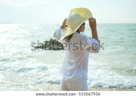 Sexy woman with white shirt and hat on the beach - glare effect