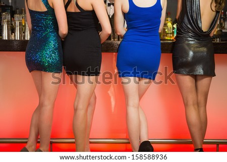 Sexy women legs standing at bar and ordering drinks - stock photo