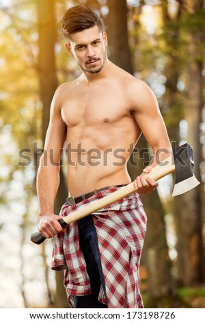 sexy woodcutter in forest