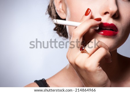 sexy young adult smoking a cigarette - stock photo