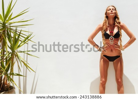 Sexy young blond fashionable woman posing in a black bikini - stock photo