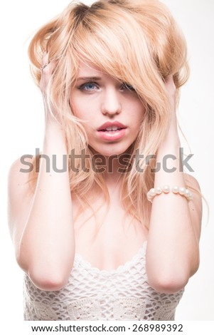 Sexy Young Blond Woman with Hands in Hair Looking Distressed, in Studio with White Background - stock photo