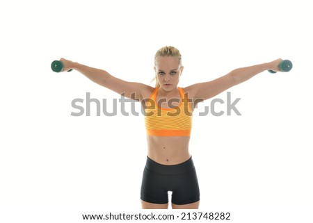 Sexy young blonde woman in bright sports bra and work-out shorts lifts small hand weights (dumbbells) in studio (fitness)