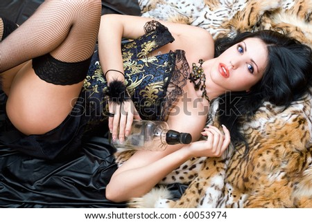 Sexy young brunette in a corset with bottle - stock photo