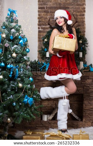 Sexy young brunette posing near christmas decorations wearing like Santa`s helper - stock photo