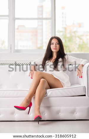 Sexy young brunette posing on the white couch - stock photo