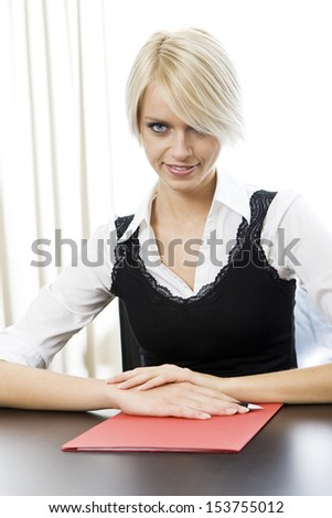Sexy young business woman with a short modern blond hairstyle sitting at a desk smiling at the camera with her fringe obscuring one eye