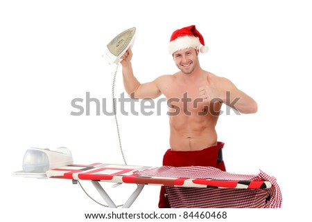 Sexy young caucasian man wearing Santa pants and hat. Cheerful man with thumb up ironing his shirt. Studio shot. White background. - stock photo