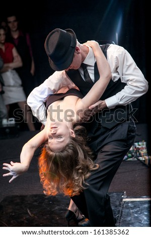 Sexy young couple dancing argentinian tango on stage - stock photo