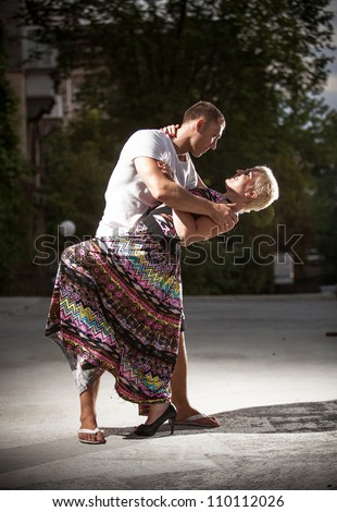 Sexy young couple dancing on the street - stock photo