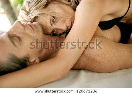 Sexy young couple hugging and being affectionate while lounging together on a tropical garden bed while on vacations in an exotic destination. - stock photo