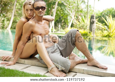 Sexy young couple hugging while lounging on the edge of an exotic swimming pool in a tropical hotel destination, outdoors. - stock photo