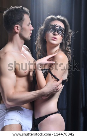 Sexy young couple in bedroom - stock photo