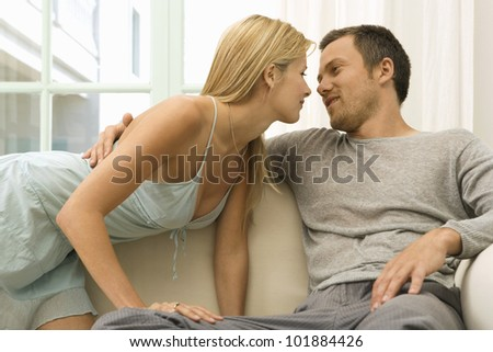 Sexy young couple kissing on home's sofa, being romantic and smiling. - stock photo