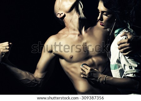 Sexy young couple of stripped man with strong muscular beautiful body and pretty brunette nurse in white smock with stethoscope standing on black studio background, horizontal picture