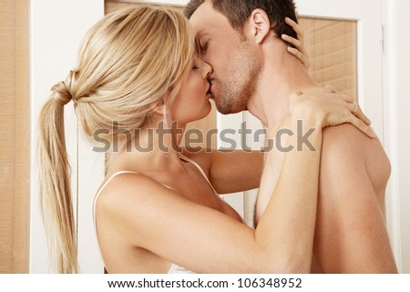 Sexy young couple passionately kissing in bedroom. - stock photo