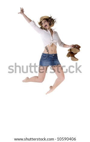 Sexy young cowgirl in a checkered blouse and straw cowboy hat jumping happily with her boots in her hand - stock photo
