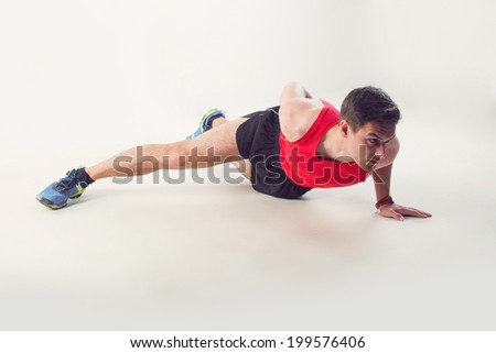 Sexy Young fashion sport muscle man, fitness model guy making push ups one hand exercise