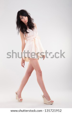 sexy young fashion woman posing while walking to a side and looking at the camera. on gray background - stock photo