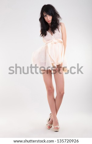 sexy young fashion woman posing with her legs crossed and one of her hands on her thigh. on gray background - stock photo