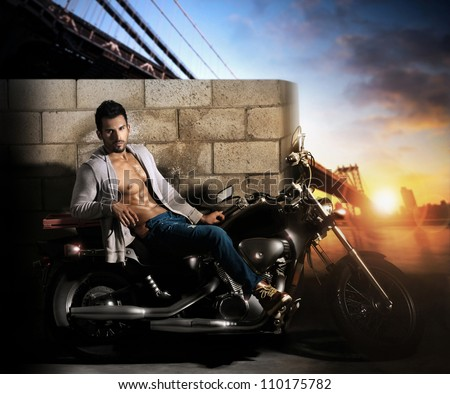 Sexy young fit male model on motorcycle outdoors at dawn