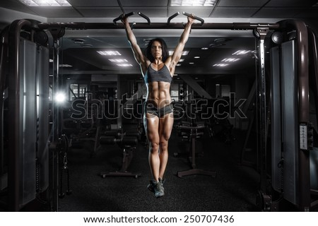 sexy young fitness girl pulls up in the gym. Brunette fitness woman in gray sport wear with perfect fitness body in gym performing abdominal exercises on the horizontal bar - stock photo
