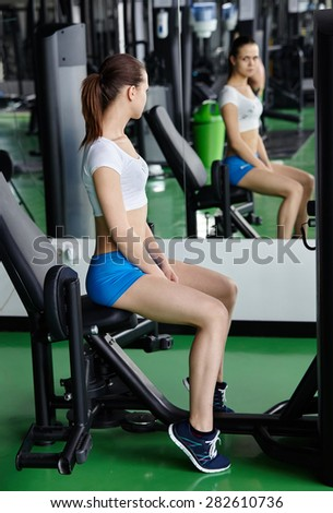 sexy young girl resting after dumbbells exercises. Fitness woman in modern gym.