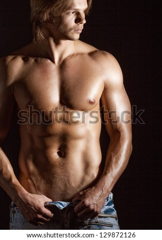 Sexy young man on a dark background - stock photo