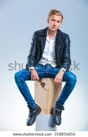 sexy young man wearing black leather jacket is posing looking at the camera with sunglasses in his hand - stock photo