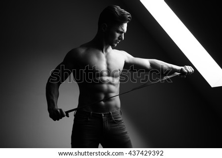 Sexy young man with muscular body and bare torso posing near window holding leather belt, black and white - stock photo