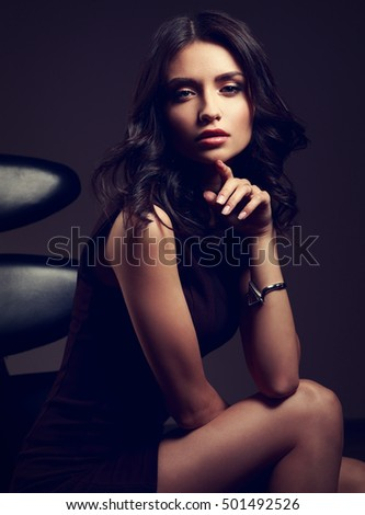 Sexy young model in brown dress sitting on the black chair and posing on dark shadow background in fashion watch on the hand