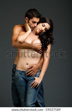 Sexy young multiracial couple in blue jeans having sensual moment - stock photo