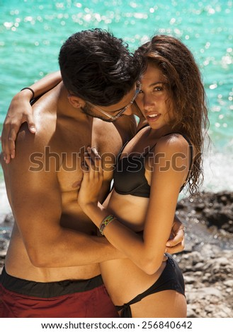 Sexy young passionate couple in bikini. Summer style. Toned in warm colors. Vertical shot - stock photo