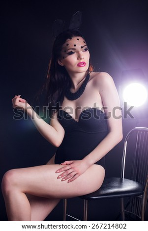 Sexy young pretty lady is wearing bunny lace ears mask with veil and black body over studio flash light - stock photo
