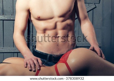Sexy young undressed sensual woman with beautiful straight body in red lace erotic lingerie lying near muscular man touching buttocks posing indoor on wooden background, horizontal picture - stock photo