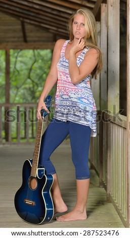 Sexy young woman - barefoot - on a wooden porch with guitar - country music series - stock photo