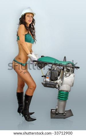 Sexy young woman construction worker dressed in lingerie, helmet, gloves and high boots. Hard work with rammer machine. - stock photo
