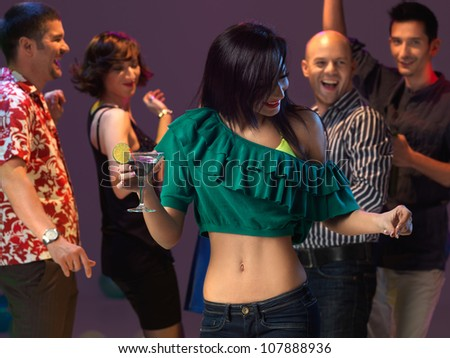 sexy, young woman dancing and drinking a cocktail on the dancefloor, in a night club - stock photo
