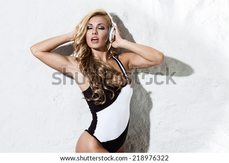 Sexy young woman dancing and listening for the music using headphones - stock photo