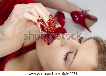Sexy young woman eating red strawberries - stock photo