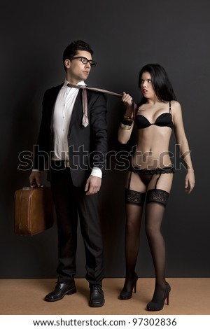 Sexy young woman grab the tie of the business man. Concept about work and pleasure - stock photo