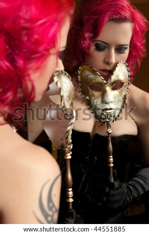 Sexy young woman holding carnival mask in front of mirror - stock photo