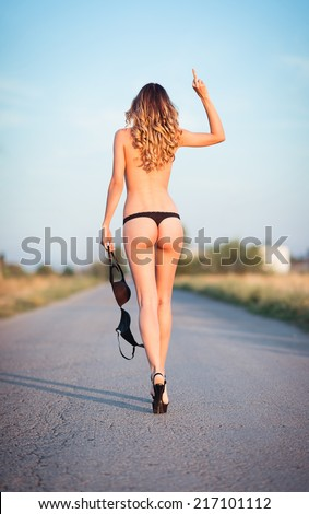 Sexy young woman in lingerie going by the road and showing offensive gesture (middle finger). Rear view - stock photo
